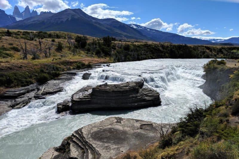 Mehrstufiger Wasserfall mit den Torres del Paine im Hintergrund