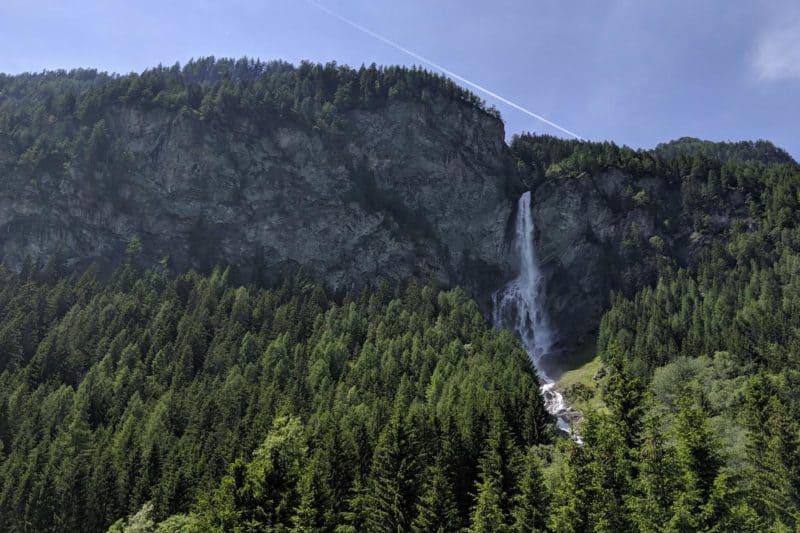 Der Jungfernsprung-Wasserfall wird von Bergen und Bäumen gerahmt.