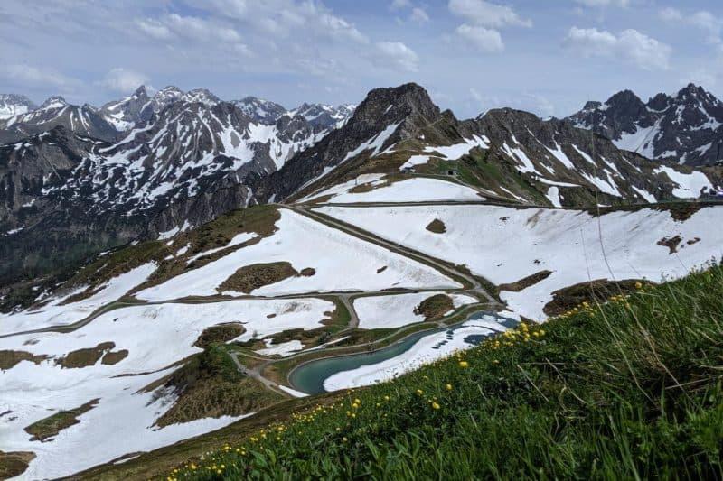 Wanderweg mit Schnee und Blumenwiese auf der Kanzelwand