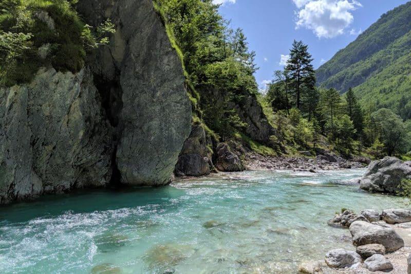 Smaragdgrünes Wasser des Soča-Flusses fließt an einem Felsen vorbei.