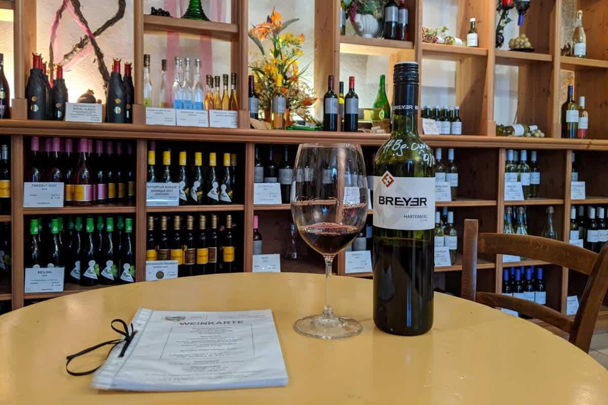 Rotweinprobe vor dem umfangreichen Weinregal der Badener Hauervinothek