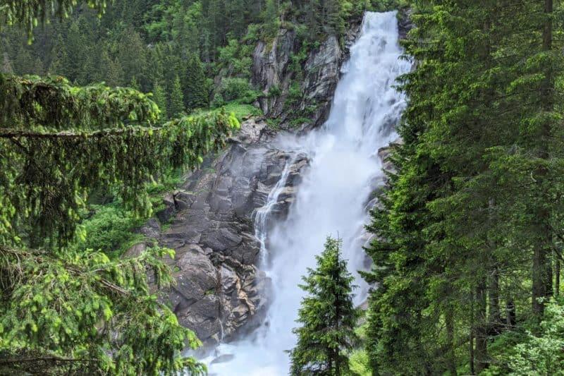 Eine Stufe der Krimmler Wasserfälle stürzt zwischen Nadelbäumen in die Tiefe